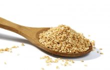 Sesame grains in large wooden spoon on white background